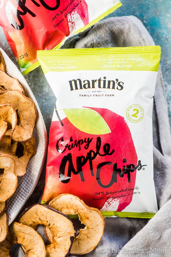 A bag of Martin's Apple Chips on a plate beside a bowl of apple guacamole.
