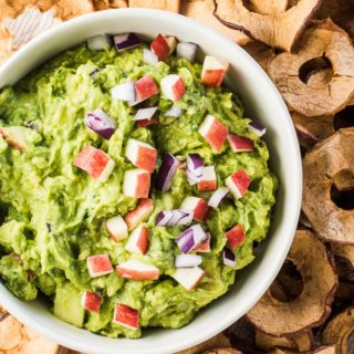 A bowl filled with apple guacamole with minced red apples and red onions on top and apple chips on the side for dipping.