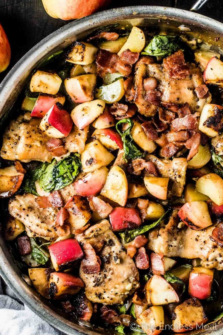 Looking down on a pan of this apple chicken recipe with a few apples on the side.