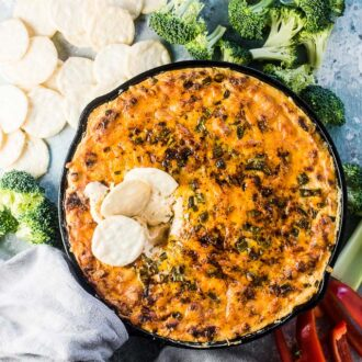 Hot cheese dip fresh out of the oven with crackers and veggies around it.