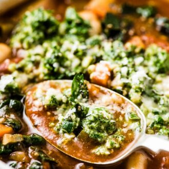 A spoonful of the best minestrone soup recipe with basil pesto on top.