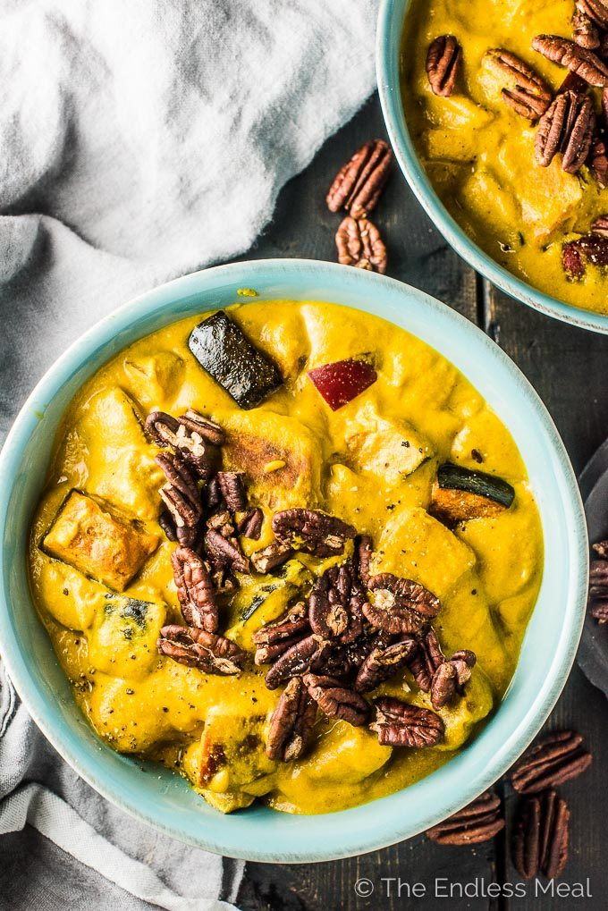 A blue bowl filled with bright yellow pumpkin curry with apples topped with toasted pecans. .