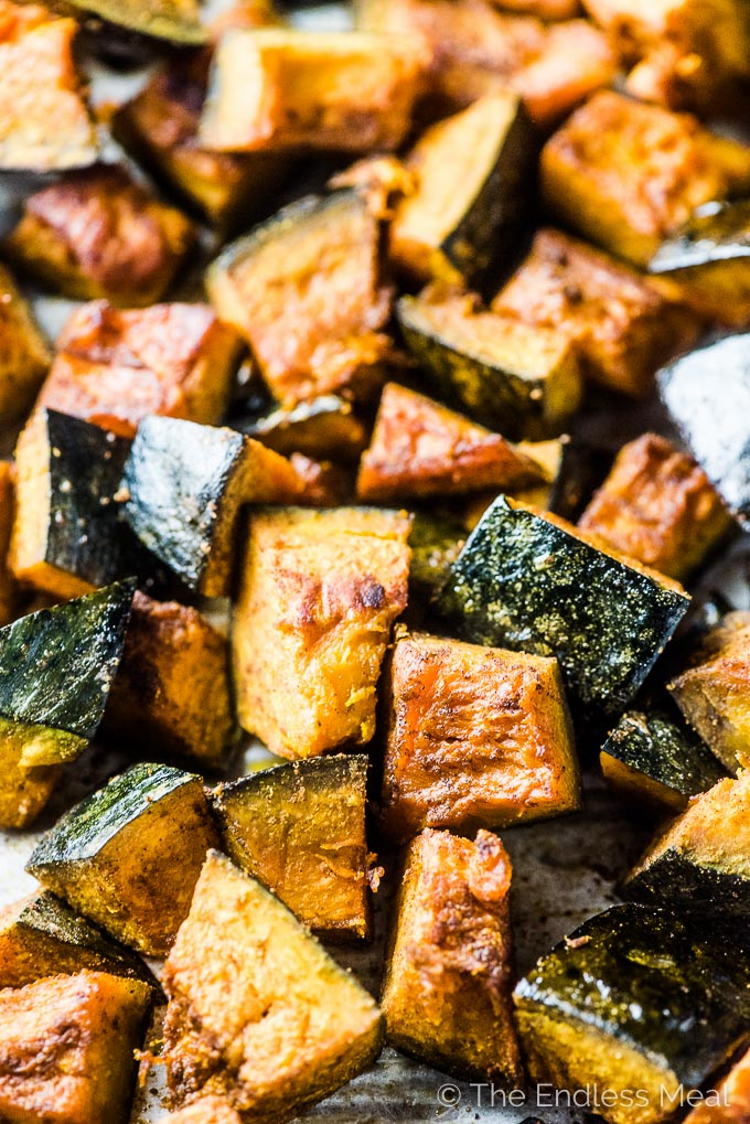Roasted spiced roasted kaboucha squash cubes with the skin on a baking tray ready to go into the pumpkin curry.