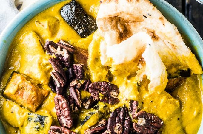 A blue bowl filled with bright yellow pumpkin curry topped with pecans and a piece of naan bread.