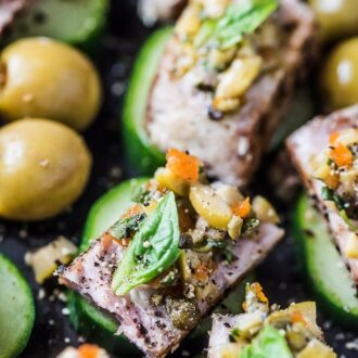 A platter of seared tuna bites on cucumber rounds with olive tapenade on top and manzanilla olives from spain on the side.