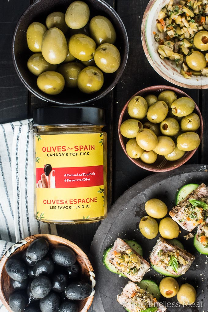 A jar of manzanilla olives from spain on a black table with bowls of olives and a plate of seared tuna bites.