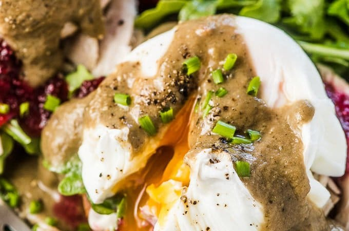 A close up of Thanksgiving Leftover Turkey Eggs Benedict with cranberry sauce and gravy on a plate with an arugula salad on the side.