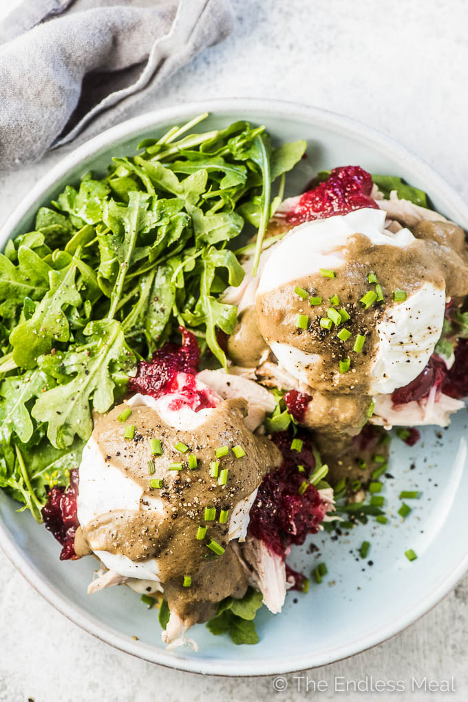 Thanksgiving Leftover Turkey Eggs Benedict with cranberry sauce and gravy on a plate with an arugula salad on the side.