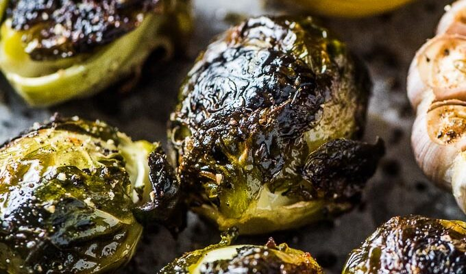 A close up of whole roasted brussels sprouts with garlic and lemon on a baking tray.