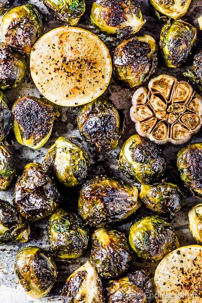 A tray of well browned whole roasted brussels sprouts with garlic and lemon fresh out of the oven.