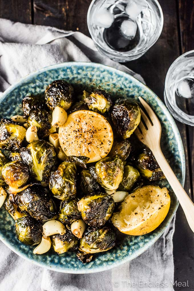 whole roasted brussels sprouts with garlic and lemon in a blue bowl with a wooden fork in it and two glasses of water on the side.