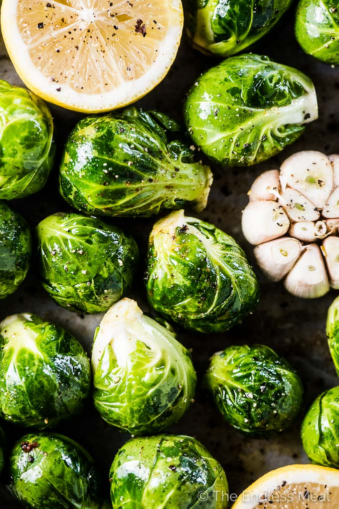 A close up of Brussels sprouts, a head of garlic, and 2 lemon halves on a baking sheet with salt, pepper, and cayenne sprinkled over the top ready to be made into whole roasted brussels sprouts with garlic and lemon.
