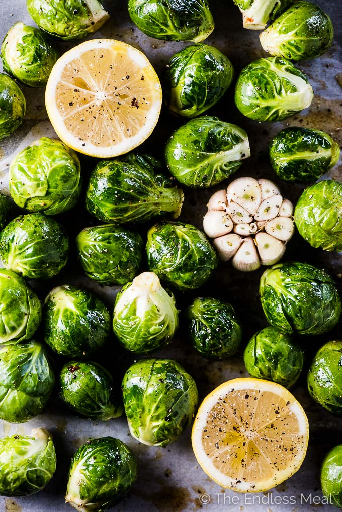 Brussels sprouts, a head of garlic, and 2 lemon halves on a baking sheet with salt, pepper, and cayenne sprinkled over the top ready to be made into whole roasted brussels sprouts with garlic and lemon.