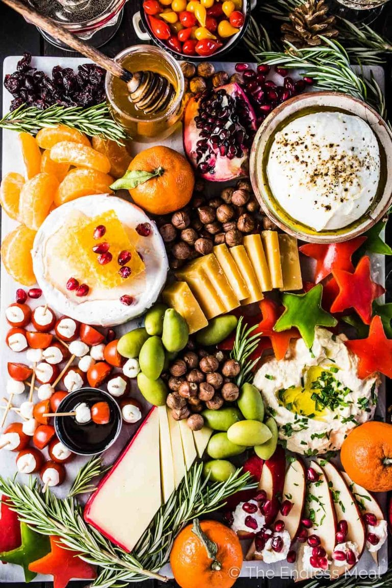 Looking down on a holiday cheese board filled with different cheeses, hummus, star shaped red peppers, tomato bites, nuts, dried fruit, honey, and more.