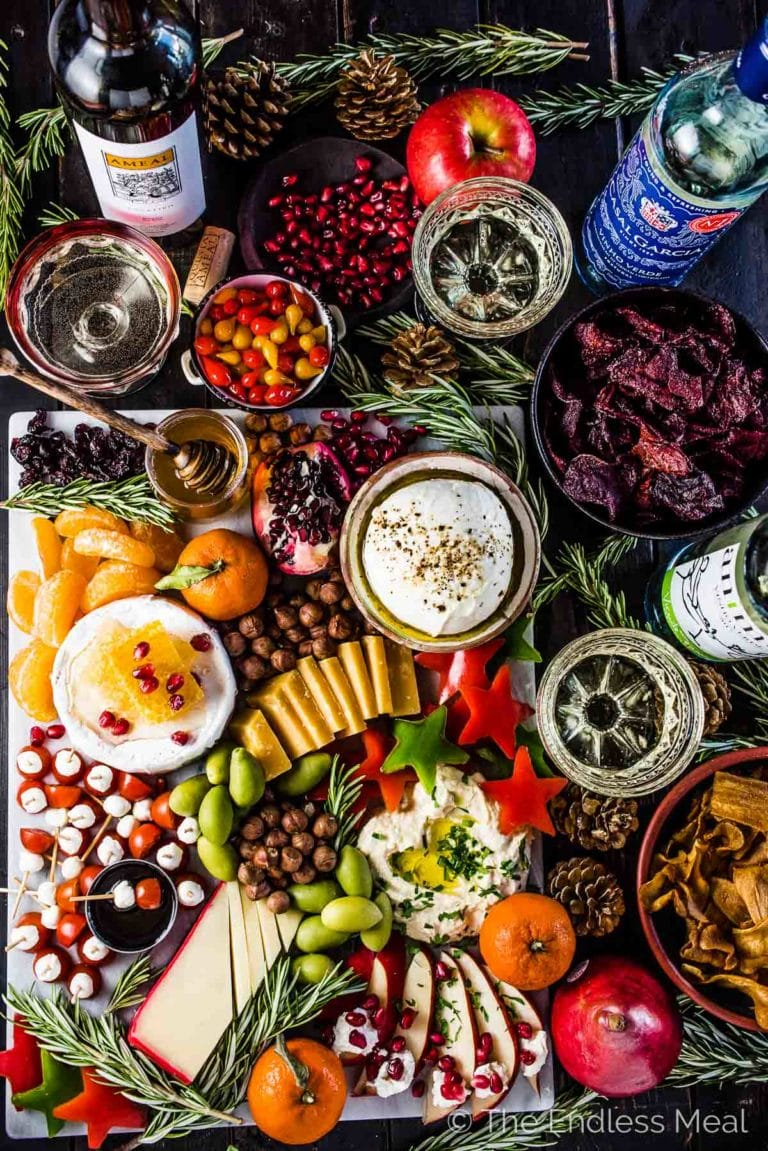 Looking down on a holiday cheese board filled with different cheeses, hummus, star shaped red peppers, tomato bites, nuts, dried fruit, honey, and more with three bottles of Vinho Verde wines at the side.