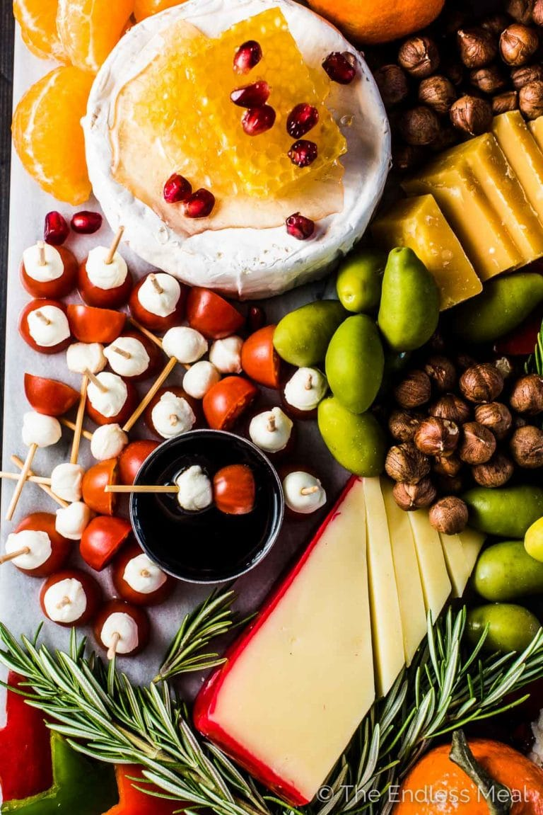 A close up of some tomato bocconcini skewers and brie cheese on the holiday cheese board.