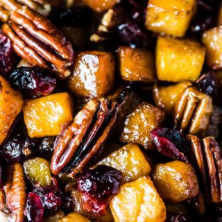 A close up of maple roasted butternut squash with cranberries and pecans on a baking sheet.