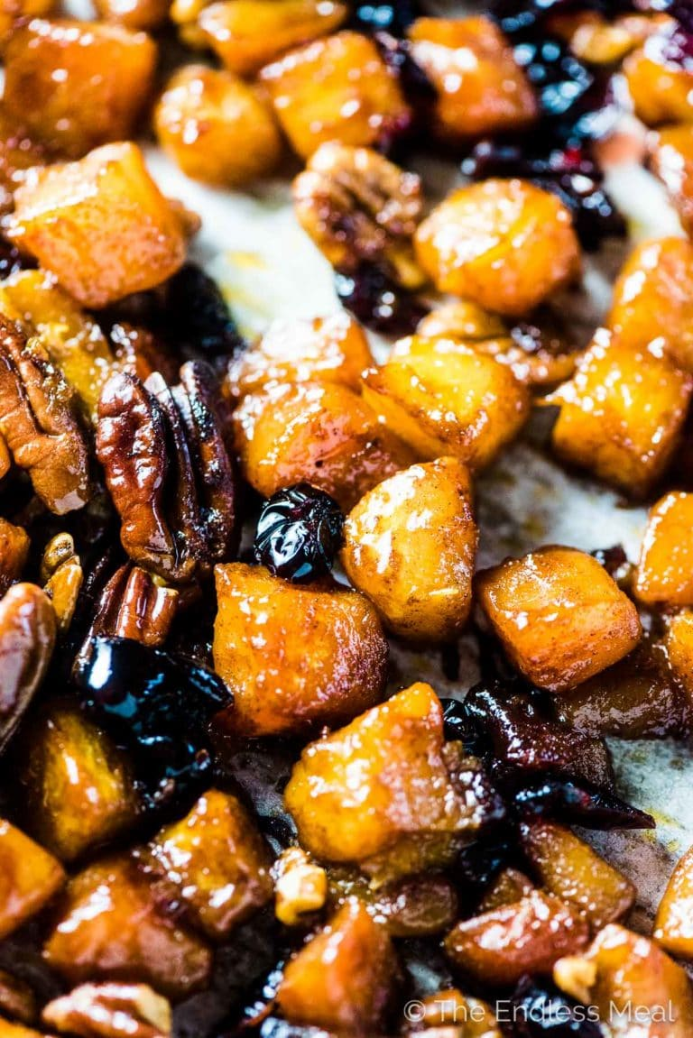 Maple roasted butternut squash with cranberries and pecans on a baking sheet.