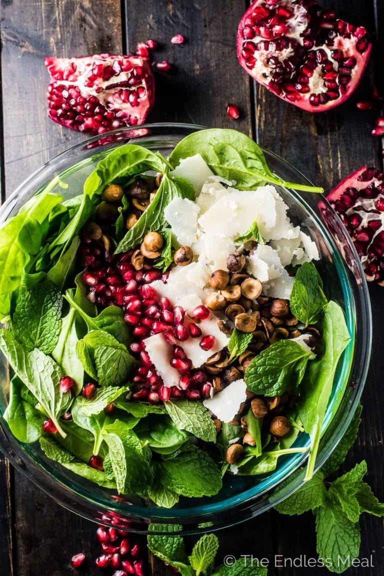 Looking down on a glass bowl with the spinach pomegranate salad with pomegranates and mint on the side.