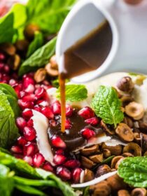 A close up of maple balsamic dressing being poured over this spinach pomegranate salad.