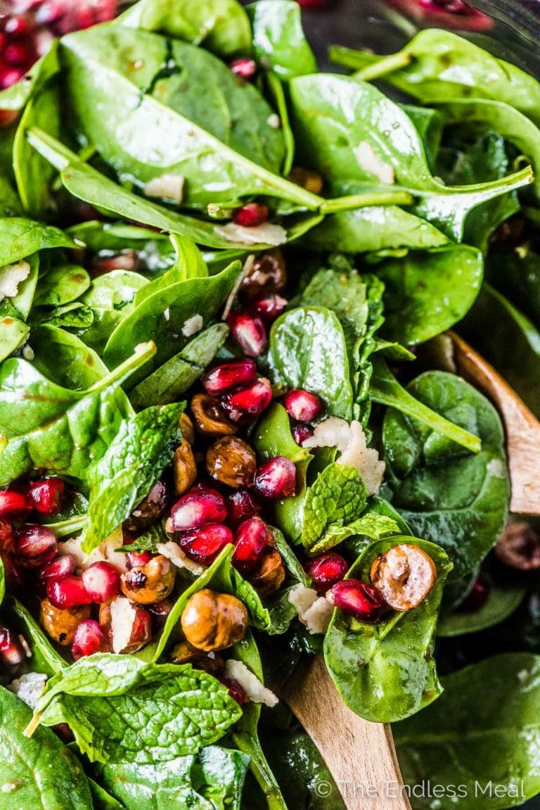 A close up of this spinach pomegranate salad with lots of pomegranates and hazelnuts.