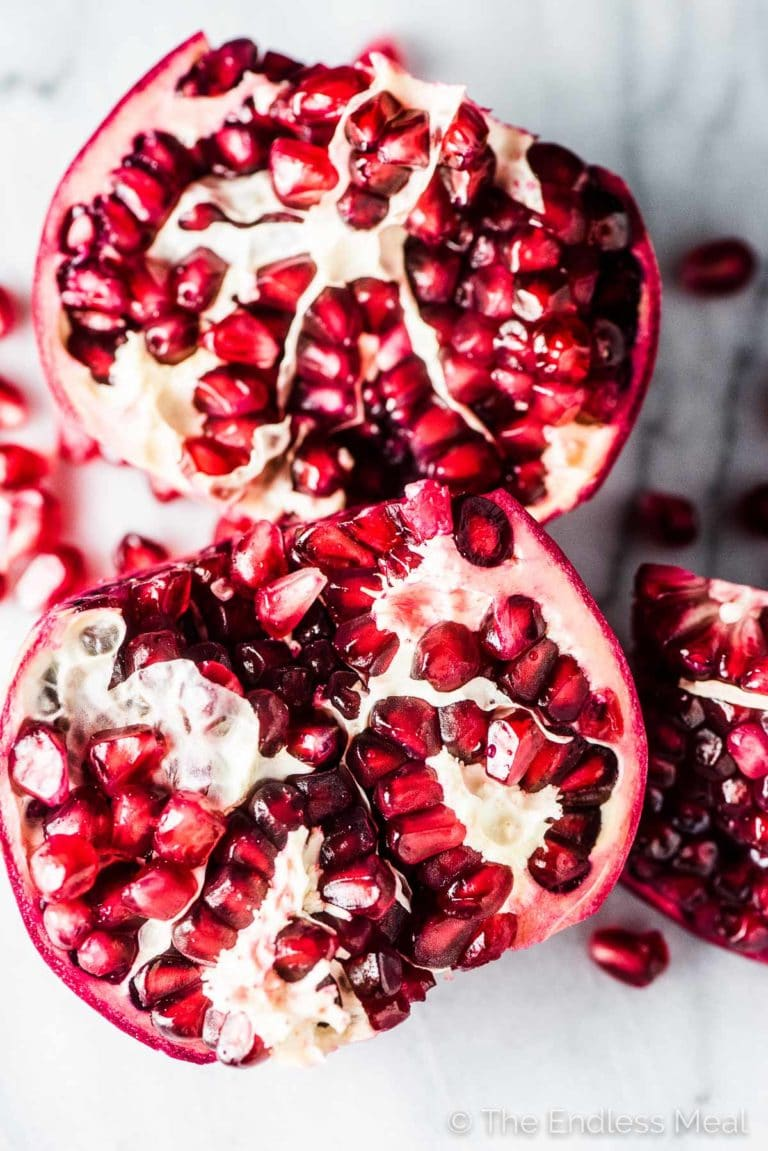 Two pomegranate halves on a marble table ready to go into the pomegranate salad.