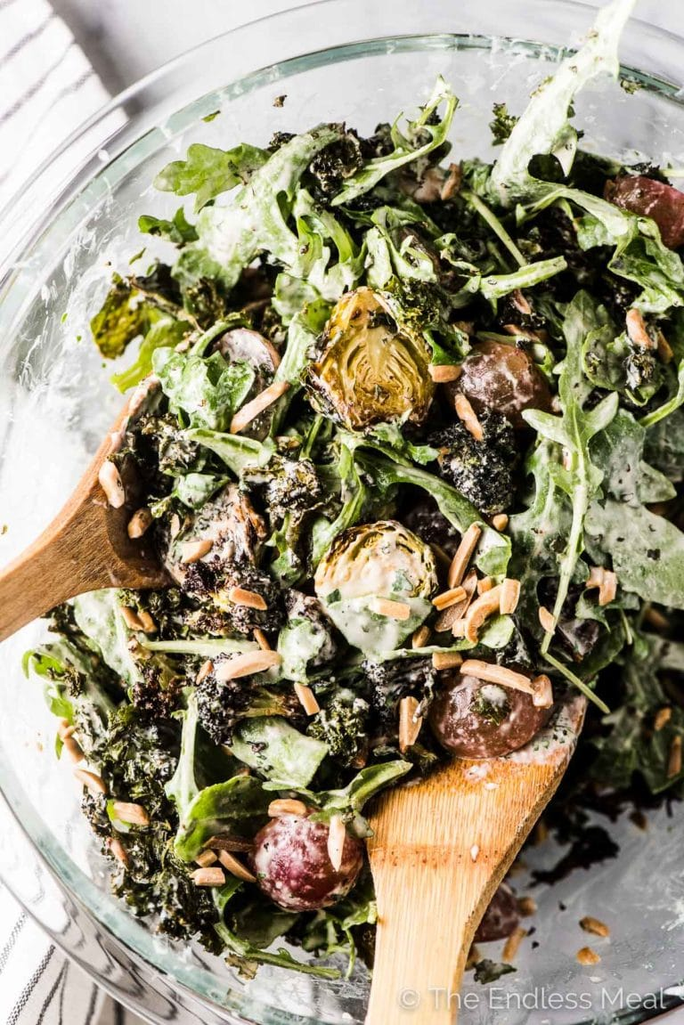Roasted winter green salad in a glass bowl with wooden salad serving spoons in it.