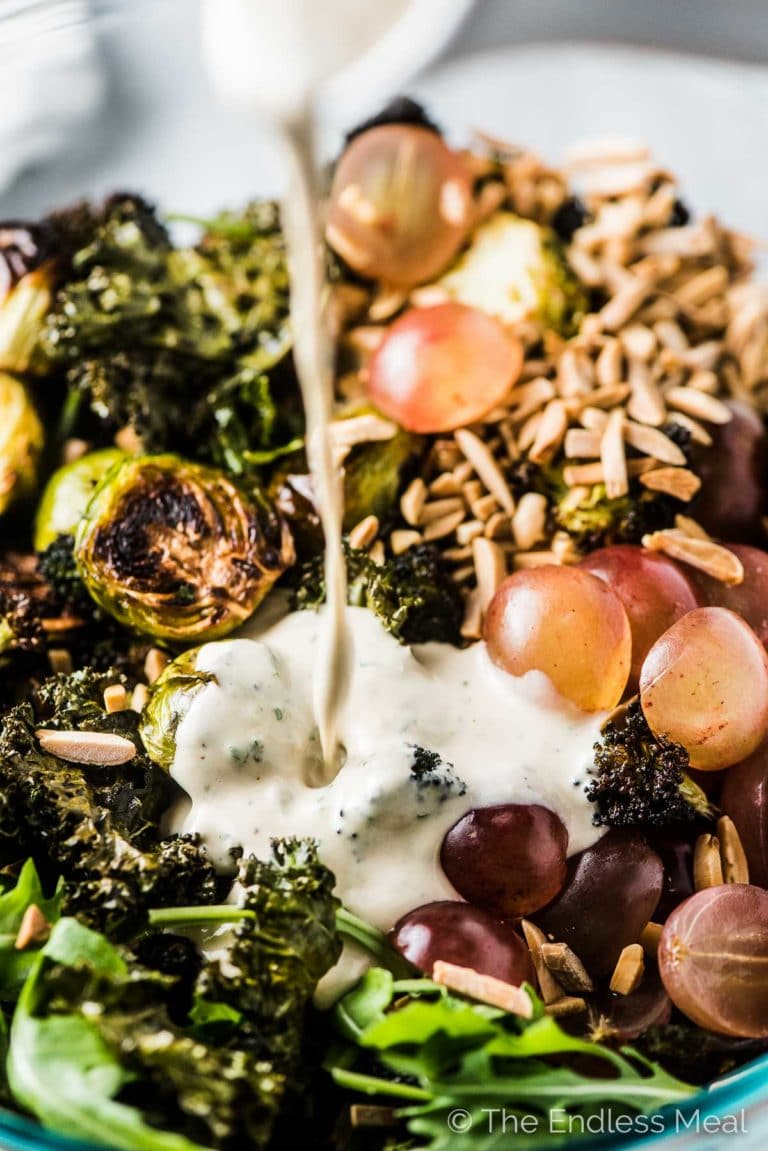 Lemon tahini dressing being poured onto winter green salad with grapes, almonds, and roasted broccoli and brussels.