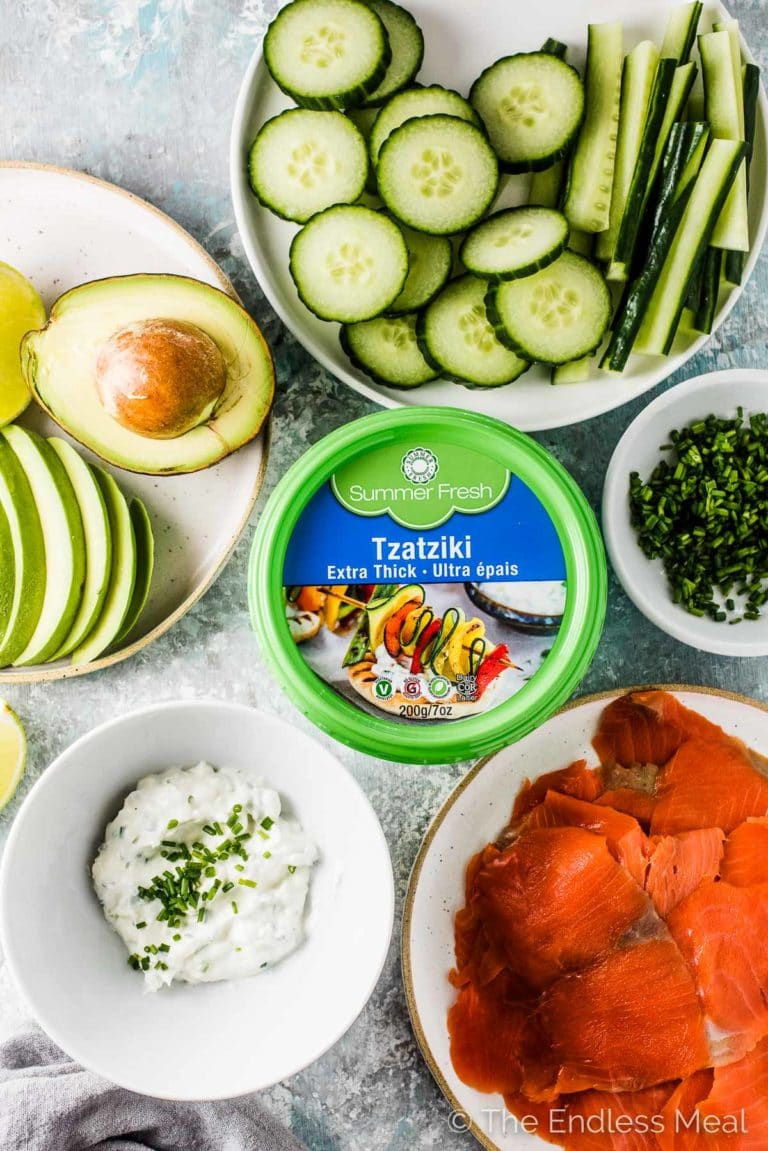 All the ingredients to make Tzatziki Avocado Salmon Rolls on a white table.