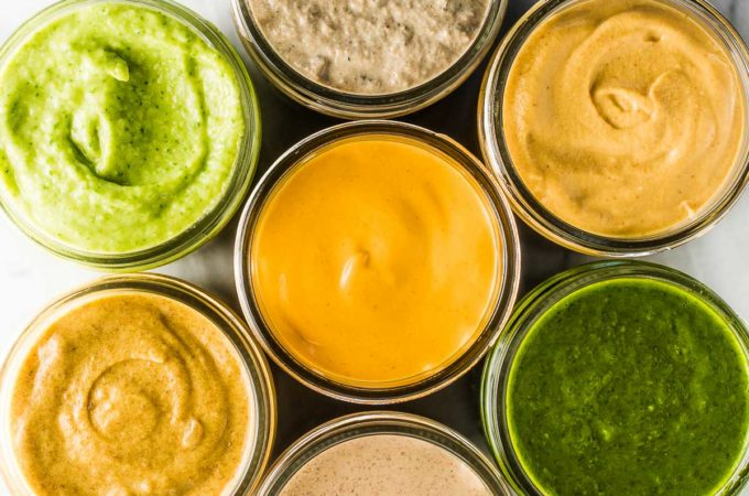 7 Whole30 sauces in glass jars on a marble table.