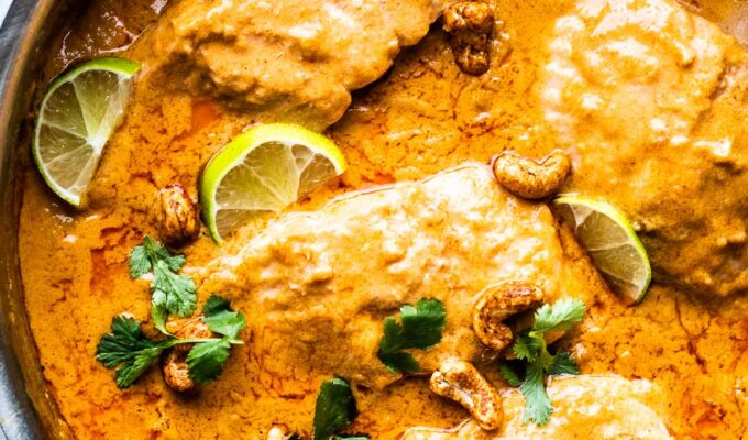 coconut salmon curry in a pan with limes and cashews.