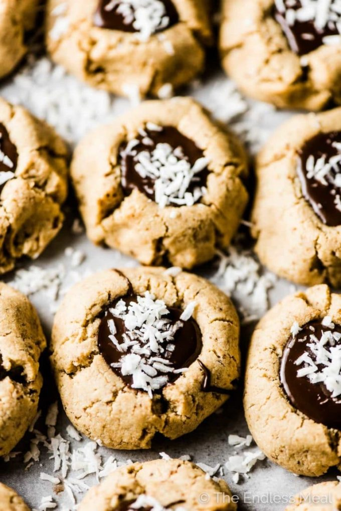Chocolate Almond Thumbprint Cookies on a tray with coconut sprinkled over top of them.
