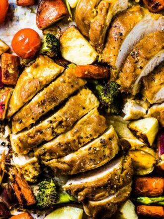 A close up of Sheet Pan Faux Honey Mustard Chicken with the chicken sliced into pieces.