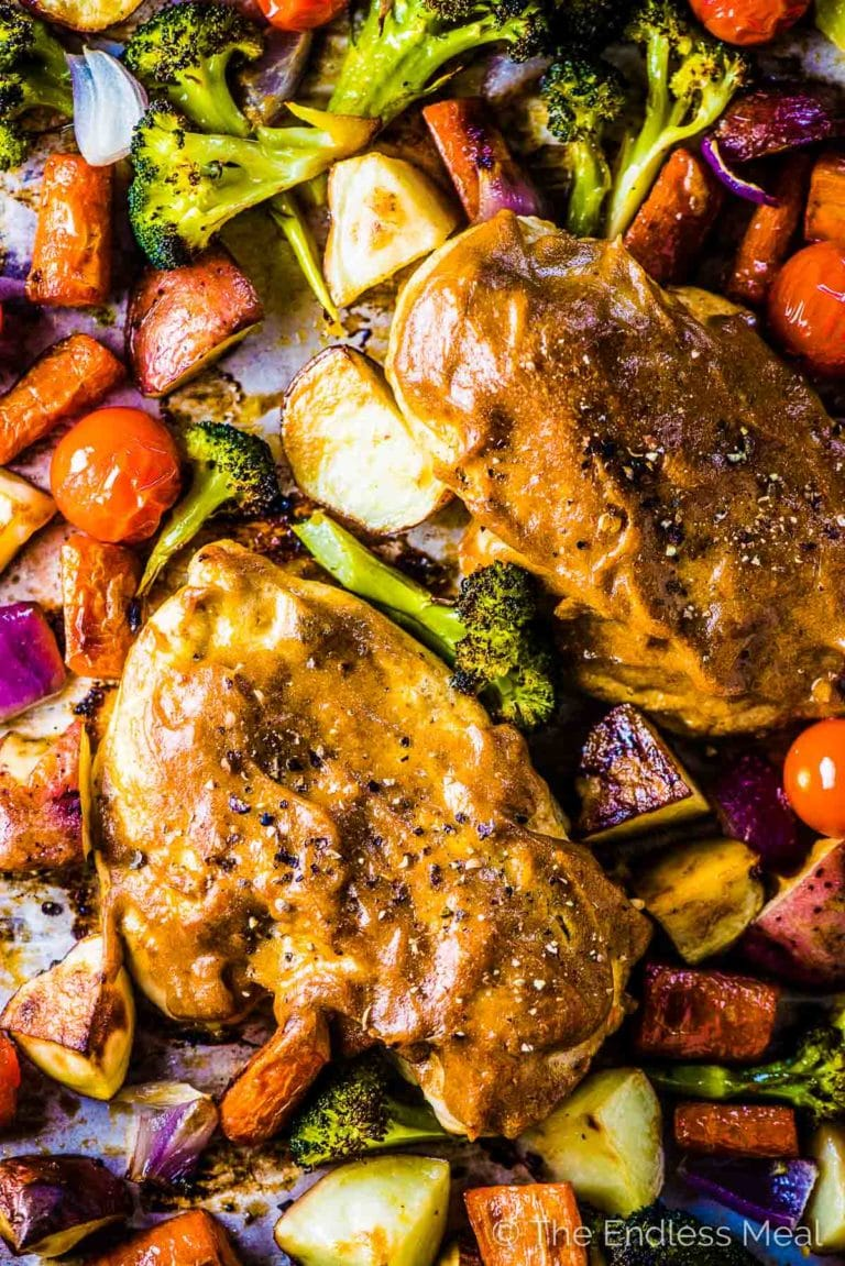 Looking down on a pan of Sheet Pan Faux Honey Mustard Chicken with lots of veggies.