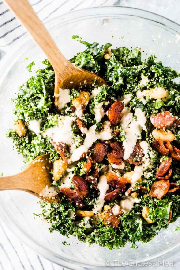 A close up of bacon kale Caesar salad with lots of crispy bacon and some dressing poured over the top.