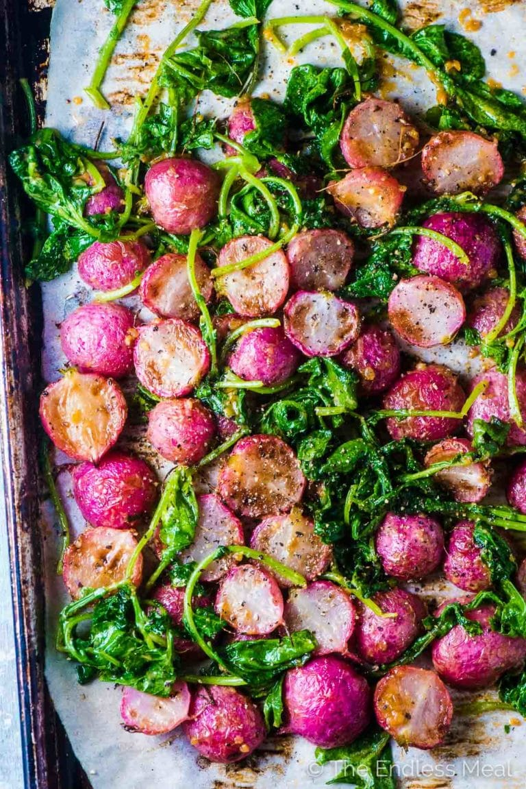 Miso Butter Roasted Radishes and radish greens on a baking sheet.