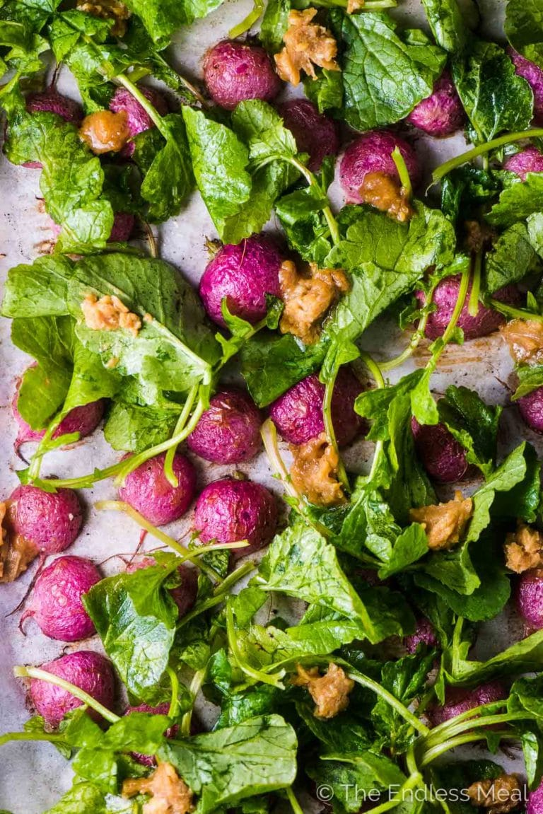 Baked radishes on a baking sheet with the radish greens on top and dotted with miso butter.