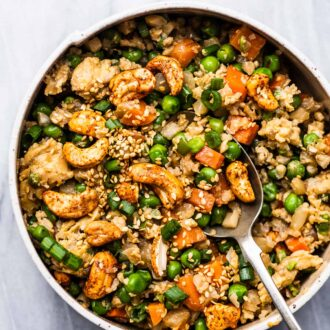 A bowl of cauliflower rice with carrots, peas, and cashews.