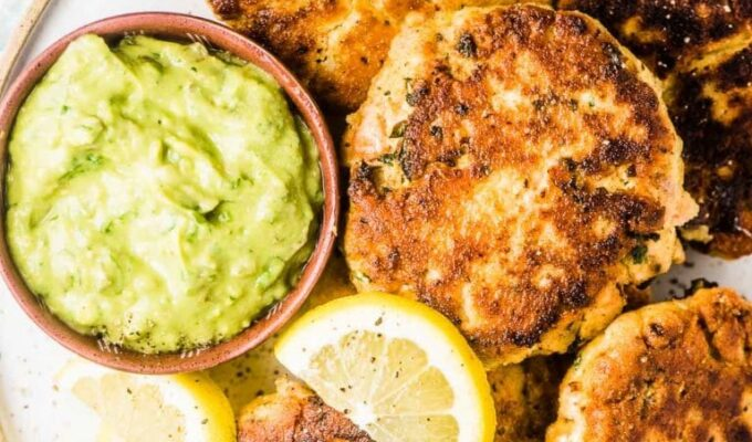 All the fish cakes from this salmon cakes recipe on a white plate with lemons and avocado tartare sauce on the side.