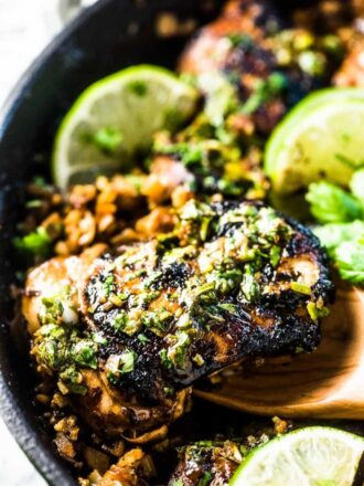 A closeup of a spoon lifting a piece of cilantro lime chicken out of a cast iron pan.