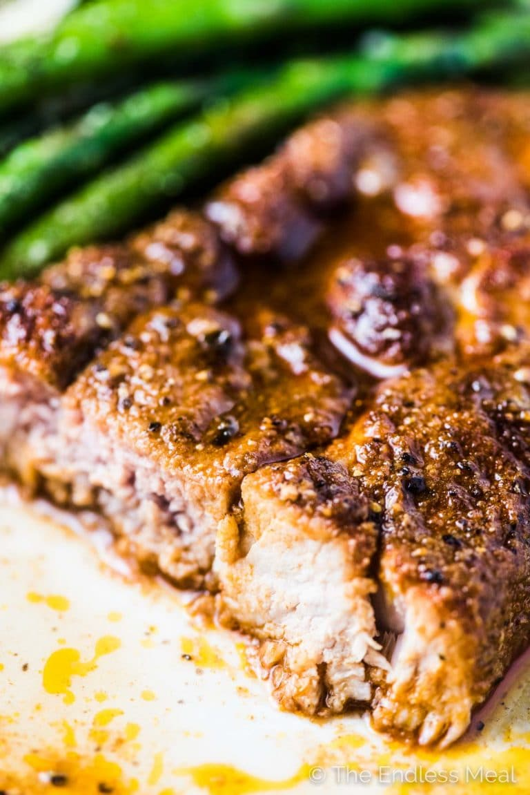 A close up of the cut side of one of these baked pork chops.