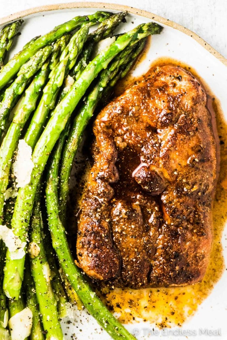A close up of this oven baked pork chop recipe on a plate with a side of asparagus.