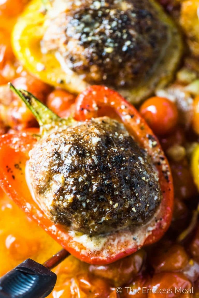 A close up of a giant meatball stuffed pepper in a casserole dish with cherry tomatoes.
