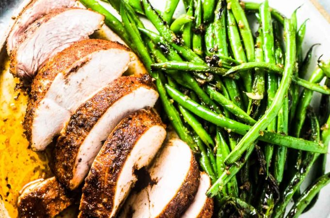 A perfect baked chicken breast cut into slices on a plate with green beans.