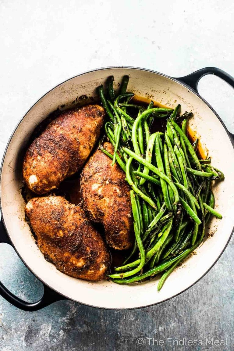 3 juicy oven baked chicken breasts in a pan with green beans on the side.