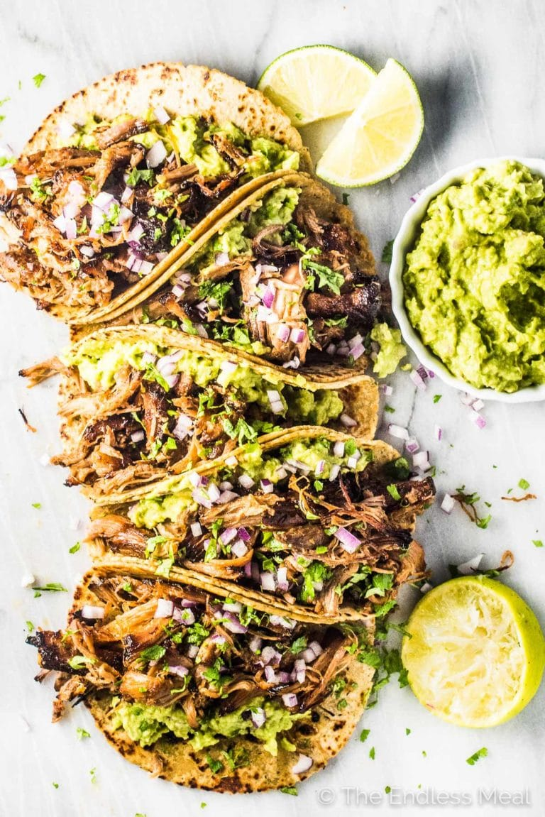 A stack of tacos de carnitas with some guacamole and a few limes on the side.