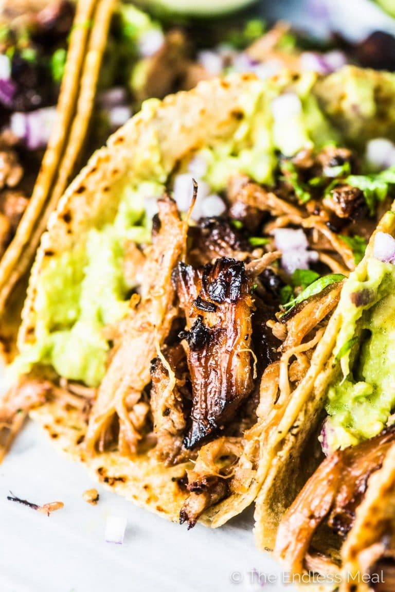 A close up side view of pulled pork tacos piled high with pulled pork and guacamole.