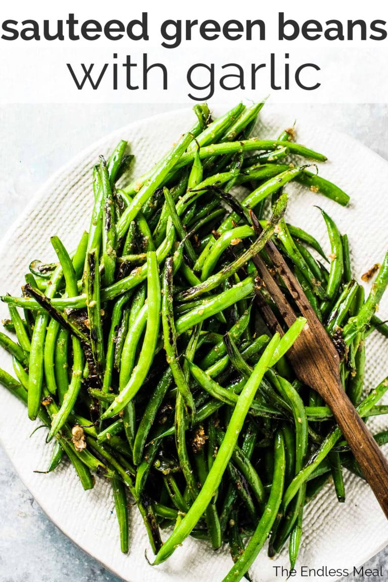 Sauteed garlic green beans on a white serving dish with the recipe title at the top.