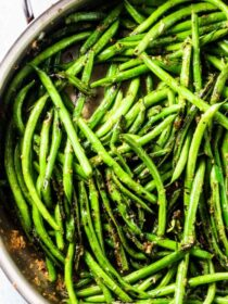 Sauteed green beans with garlic in a skillet.