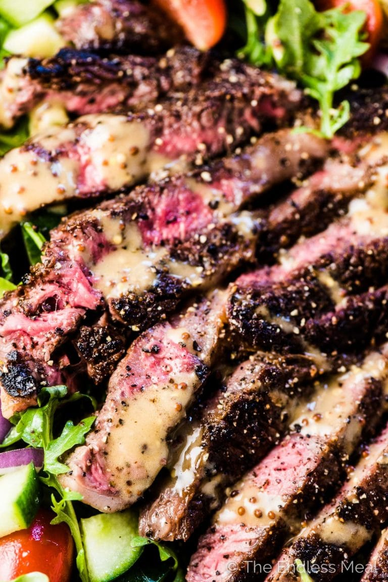 A close up of this steak salad with perfectly cooked sliced steak on top of veggies with some creamy balsamic dressing over the top.
